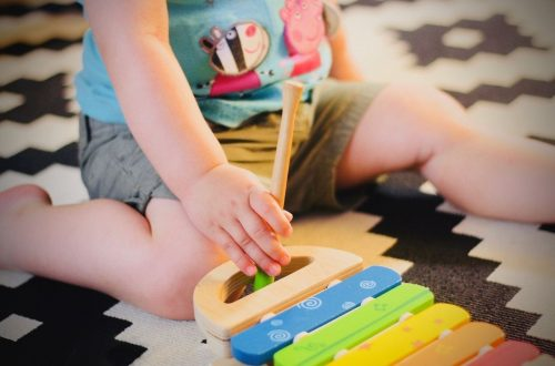toddler playing on a xylophone