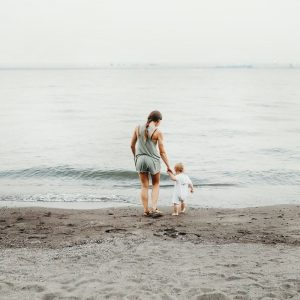 mom and child holding hands on the beach